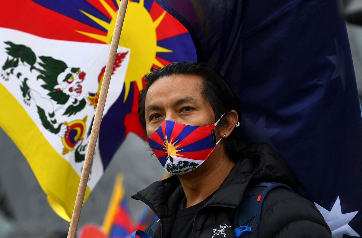 An activist stands with the Tibetan flag as he joins a protest by members the local Hong Kong, Tibetan and Uyghur communities in Melbourne on June 23, 2021, calling on the Australian government to boycott the 2022 Beijing Winter Olympics over China's human rights record.