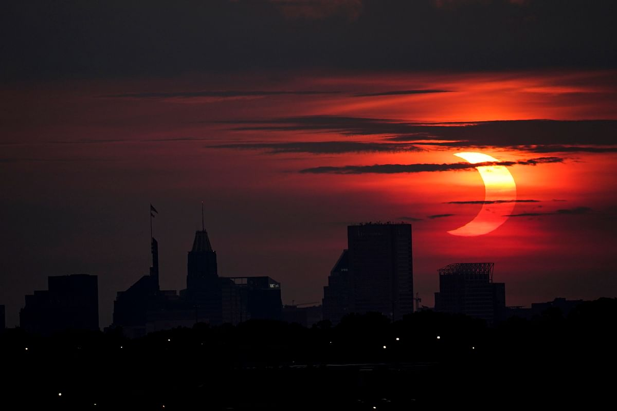 A partial solar eclipse rises over the Baltimore skyline, Thursday, June 10, 2021, seen from Arbutus, Md in the USA.