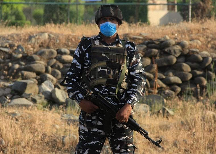CRPF personnel stands guard on a road in outskirts of Srinagar