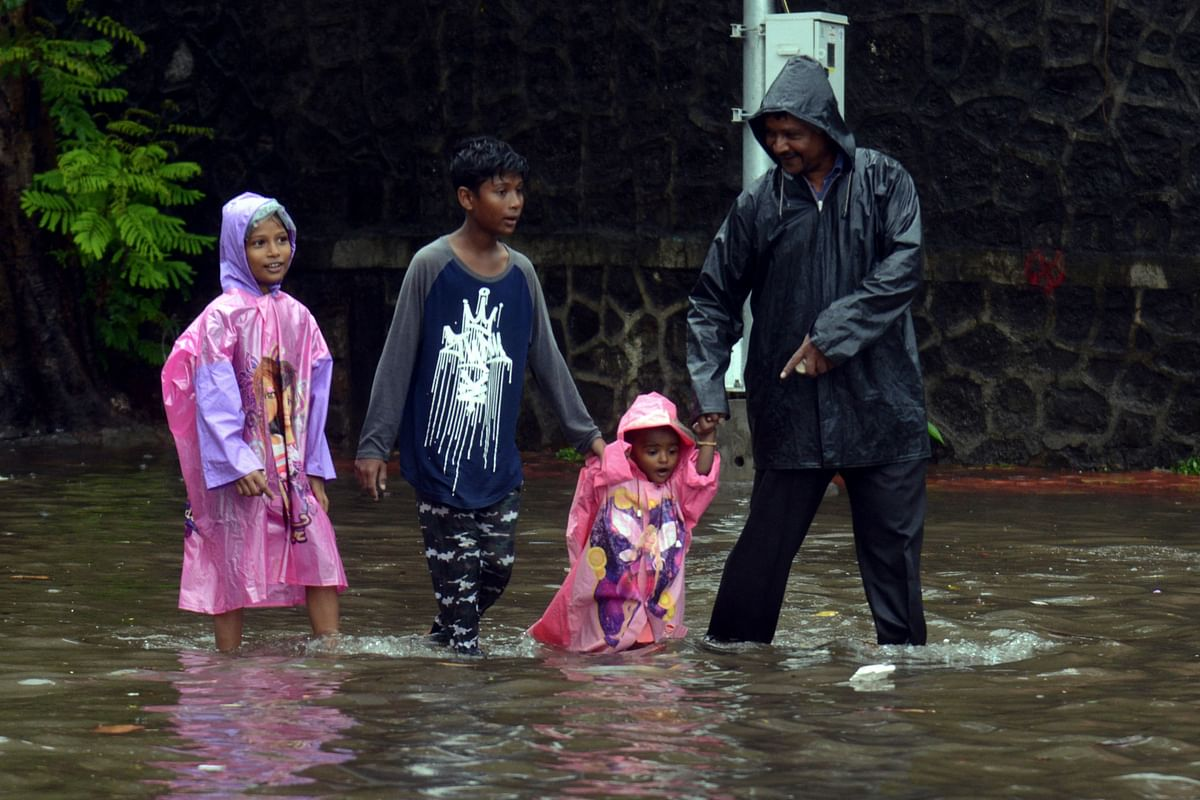 A family wades along a waterlogged street following a heavy monsoon rainfall in Mumbai on June 9, 2021.