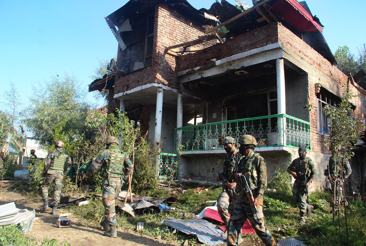 Army soldiers stand guard outside the house that was damaged during a gunfight between security forces and militants in Maloora locality on the outskirts of Srinagar, Jammu & Kashmir.
