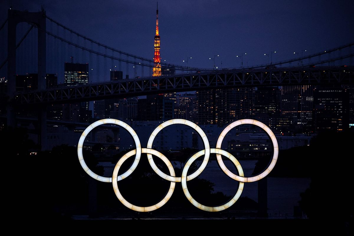 A general view shows the Olympic Rings lit up at dusk, with the Rainbow bridge and the Tokyo Tower in the background, on the Odaiba waterfront in Tokyo on June 23, 2021.