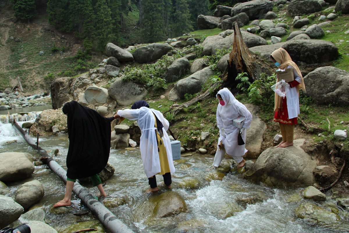 Healthcare workers cross a stream to reach to tge forest area to inoculate nomadic people with a coronavirus disease (COVID-19) vaccine during a vaccination drive in central Kashmir's Budgam district.