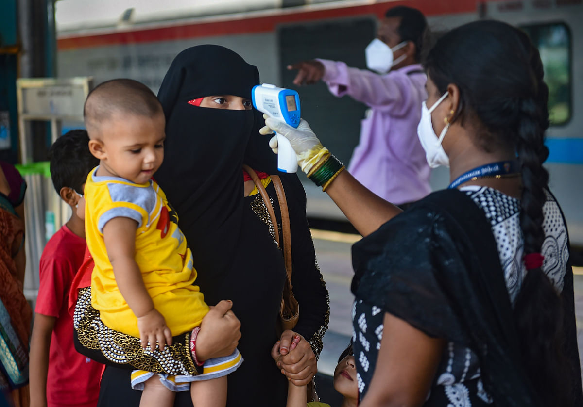 Mumbai: A BMC health worker does thermal screening of a passenger for COVID-19 test, at Dadar railway station in Mumbai, Thursday, June 3, 2021.