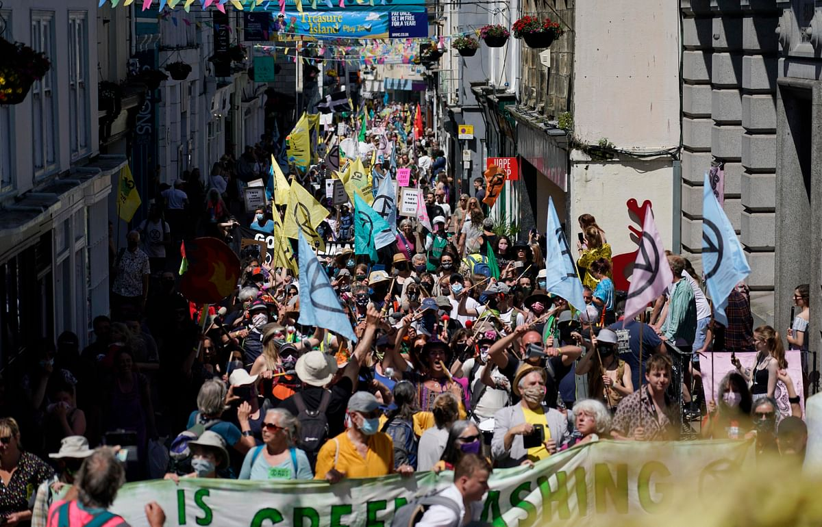 Activists march through the streets in during a demonstration around the meeting of the G7 in Falmouth, Cornwall, England, Saturday, June 12, 2021. Leaders of the G7 gather for a second day of meetings on Saturday, in which they will discuss COVID-19, climate, foreign policy and the economy.