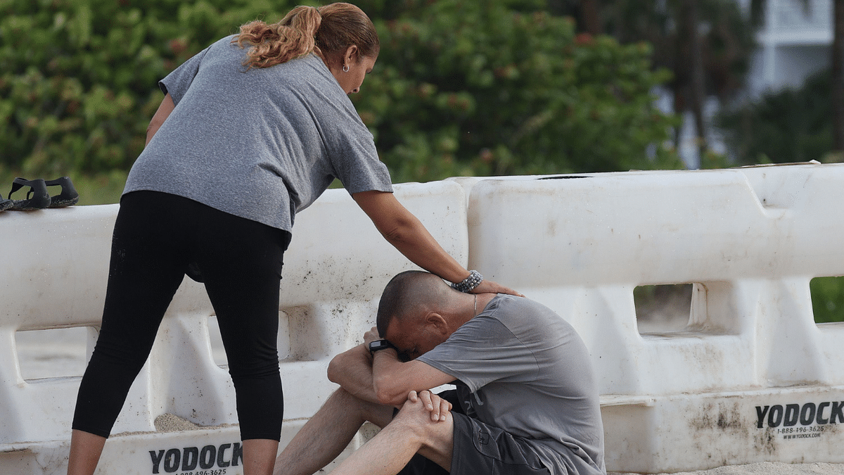 A couple becomes emotional as they visit pray near the partially collapsed 12-story Champlain Towers South condo building on June 26, 2021 in Surfside, Florida.