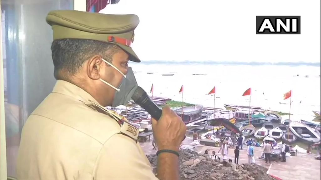 Police personnel deployed at Ganga Ghat on the occasion of the Ganga Dussehra festival, made repeated announcements to adhere to Covid-19 protocols in Varanasi, Sunday, June 20, 2021.