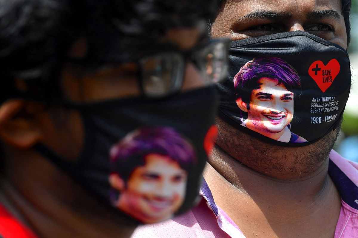 Fans of late Bollywood actor Sushant Singh Rajput wear masks depicting his photograph as they gather to commemorate his first death anniversary, in Mumbai on June 14, 2021.
