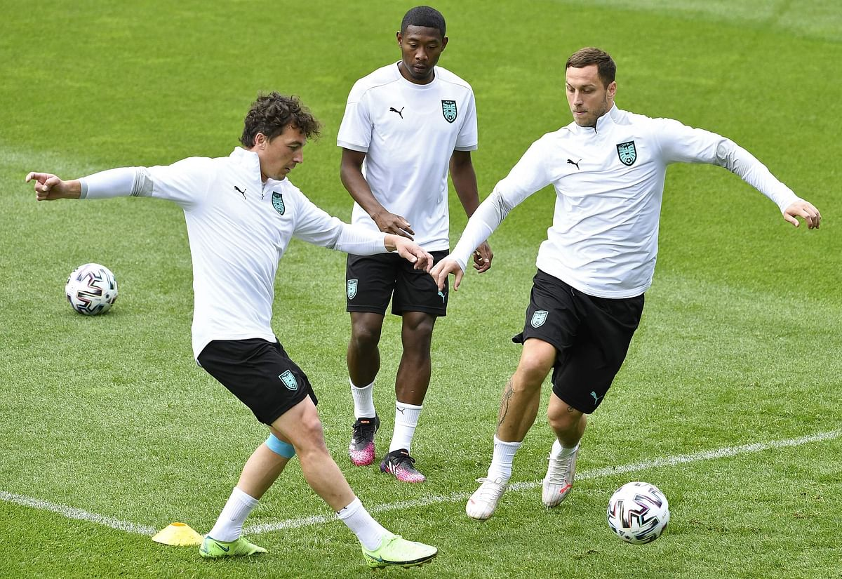 Austria's defender David Alaba (back) looks at Austria's midfielder Julian Baumgartlinger (L) and Austria's forward Marko Arnautovic playing a ball during their training session at the team's base camp in Seefeld on Saturday