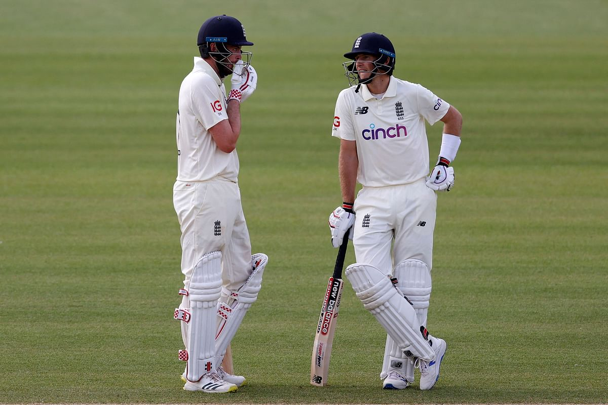 Englands Dom Sibley (L) talks to Englands Joe Root on the fifth day of the first Test cricket match between England and New Zealand at Lords Cricket Ground in London on June 6, 2021.