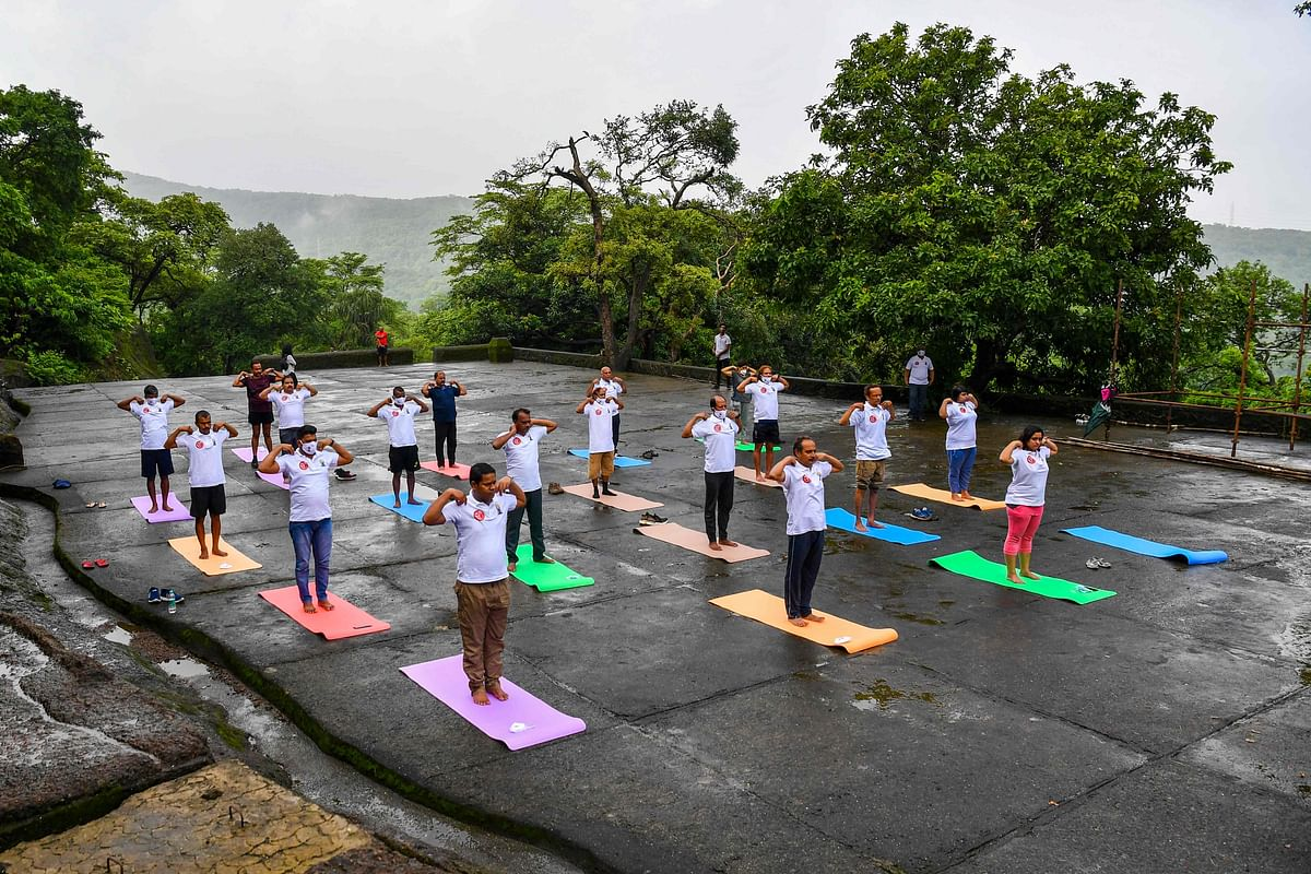 People take part in a yoga session at the Kanheri Caves on the outskirts of Mumbai on June 21, 2021, to mark International Yoga Day.