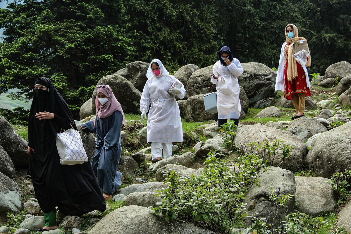 Healthcare workers head to a hut to inoculate nomadic tribes during a COVID-19 vaccination drive in the forest area of Central Kashmir's Budgam district.