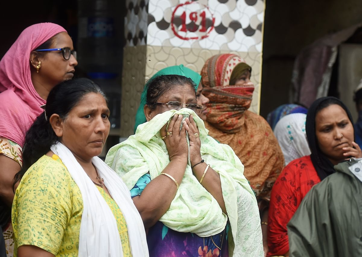 Relatives and friends react on the death of a person, after a single-storey house collapsed on another structure in Malwani area on Wednesday night, in Mumbai, Thursday, June 10, 2021. At least eight children and three adults were killed and seven other people injured in the mishap.