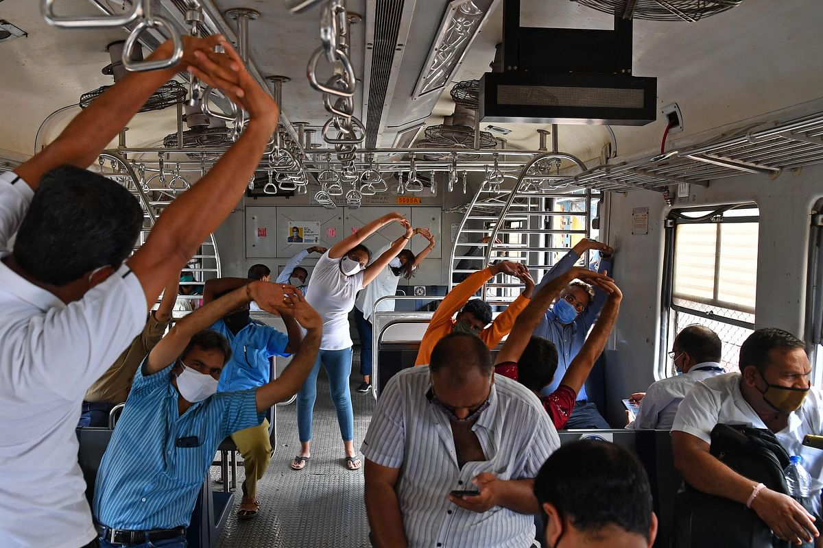Commuters take part in a yoga session inside a train coach in Mumbai on June 21, 2021, to mark International Yoga Day.