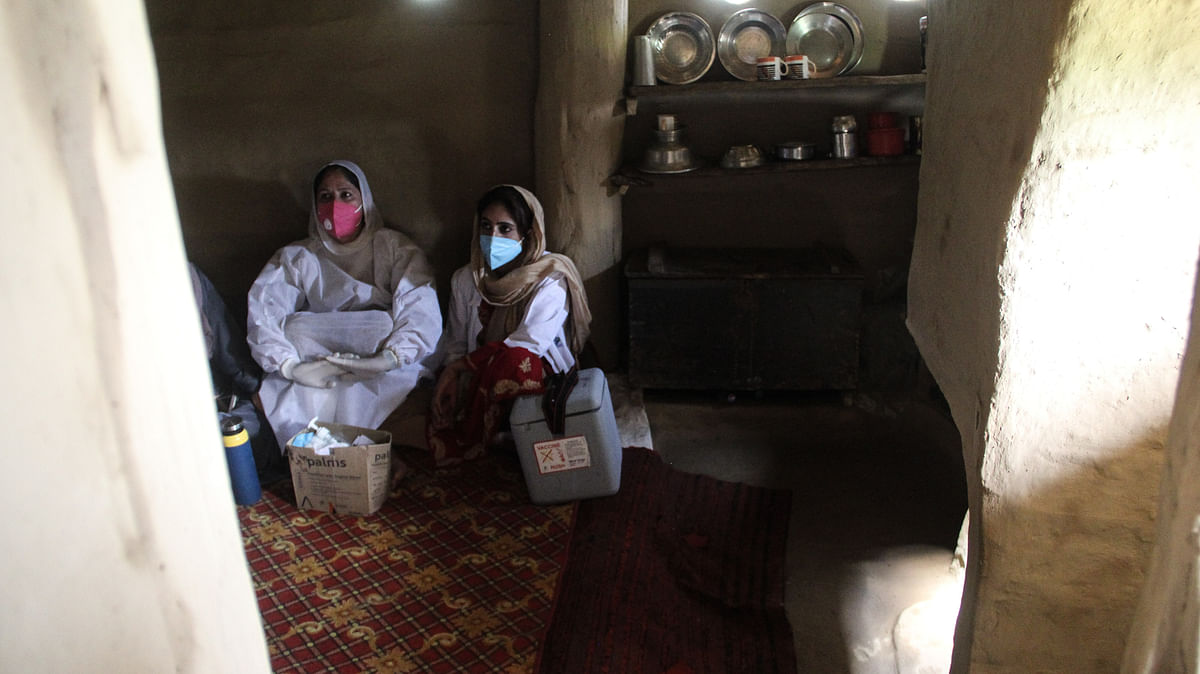 Healthcare workers rest inside a mud house during the vaccination drive in the forest area of Central kashmir's Budgam district.