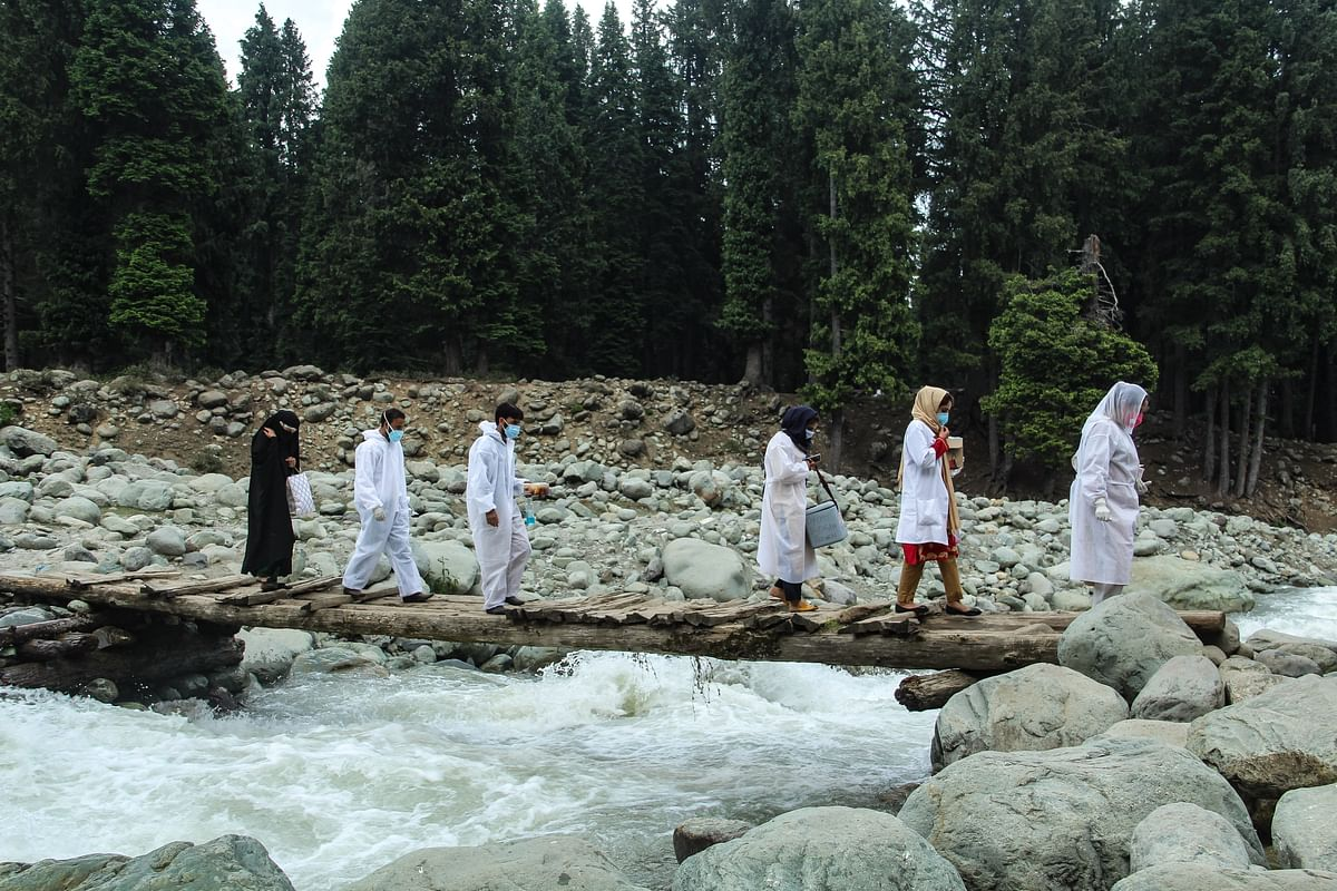 Healthcare workers cross a stream to reach the forest area in central Kashmir's Budgam district to inoculate nomadic with a coronavirus disease (COVID-19) vaccine during a vaccination drive.