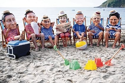 Oxfam activists wearing papier mache heads depicting G7 leaders perform during a protest at Swanpool Beach near Falmouth in Cornwall, England.