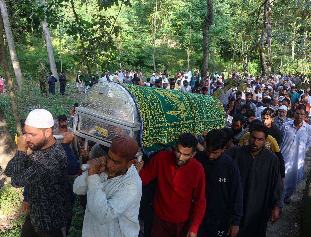 People carry the body of the daughter of an policeman, who was killed along with her father and mother by militants.