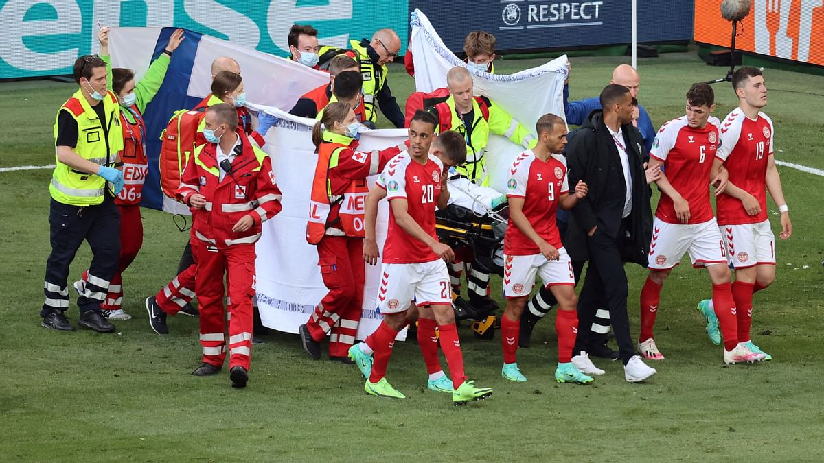 Denmarks players gather as paramedics attend to midfielder Christian Eriksen (not seen) during the UEFA EURO 2020 Group B football match between Denmark and Finland at the Parken Stadium in Copenhagen on June 12, 2021.