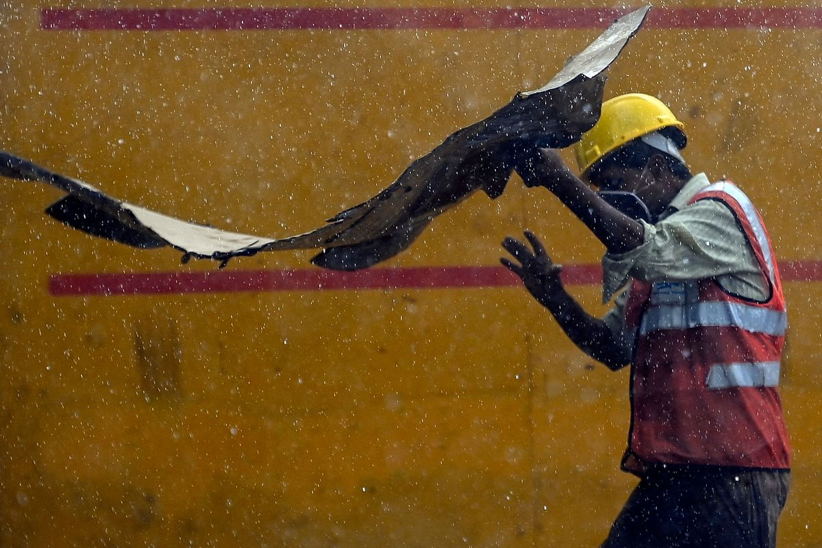 A construction worker holds a cardboard sheet to shelter during a monsoon rainfall, near India Gate in New Delhi on June 17, 2021.