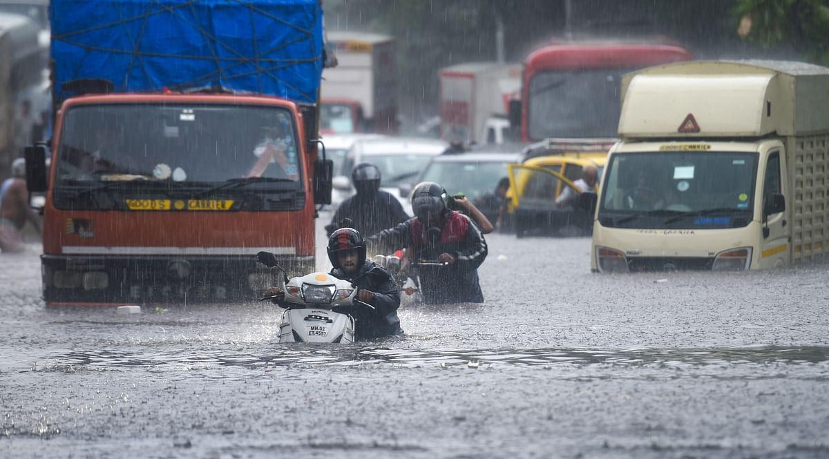 Vehicles make their way through the waterlogged road during heavy rain, at Kings Circle, in Mumbai, Wednesday, June 9, 2021