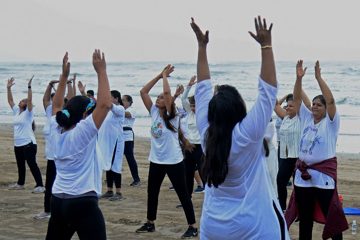People take part in a yoga session at the Juhu beach of Mumbai on June 21, 2021, to mark International Yoga Day.