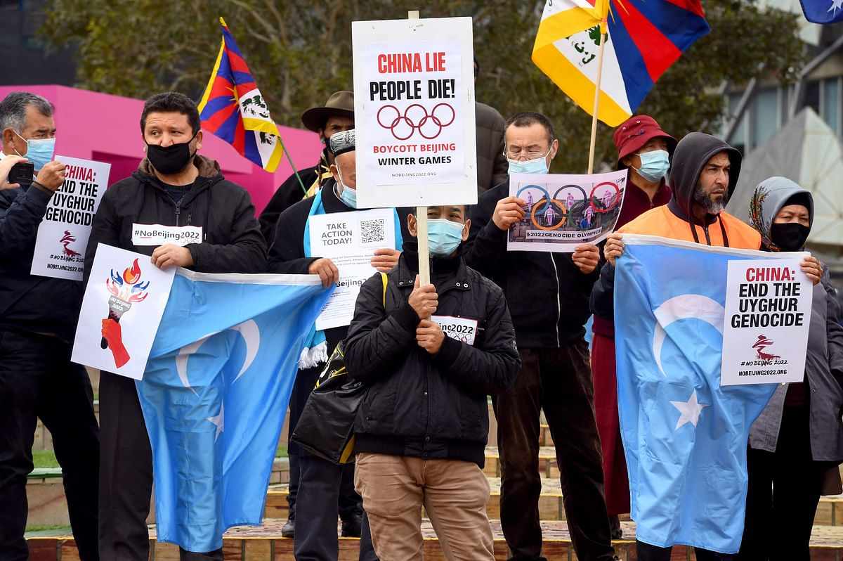 Activists including members of the local Hong Kong, Tibetan and Uyghur communities hold up banners and placards in Melbourne on June 23, 2021, calling on the Australian government to boycott the 2022 Beijing Winter Olympics over China's human rights record.