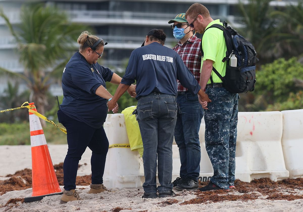People pray together near the partially collapsed 12-story Champlain Towers South condo building on June 26, 2021 in Surfside, Florida.