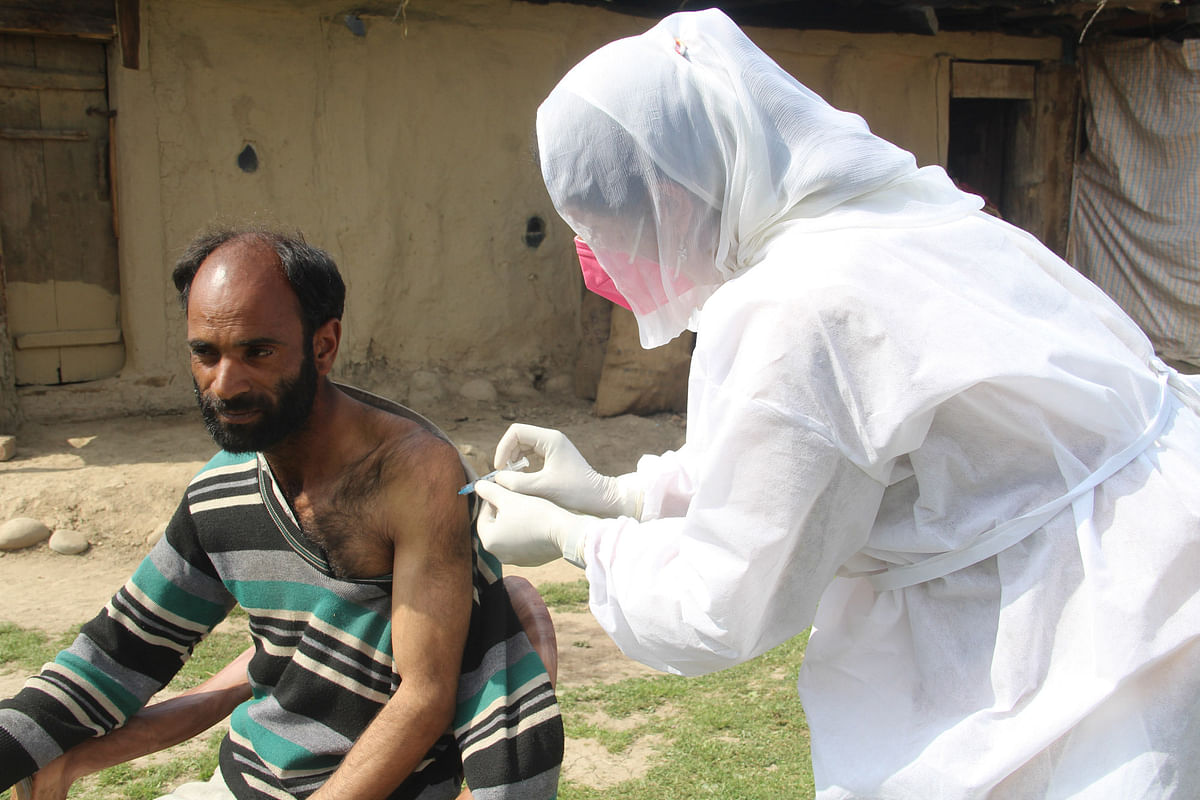 A health worker administers a COVID-19 vaccine to an elderly nomad man in a remote village of Central Kashmir's Budgam district.