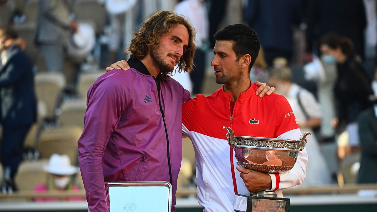 Novak Djokovic (R) and Stefanos Tsitsipas pose with their trophy at the end of their men's final tennis match on Day 15 of The Roland Garros 2021 French Open tennis tournament in Paris on June 13, 2021.