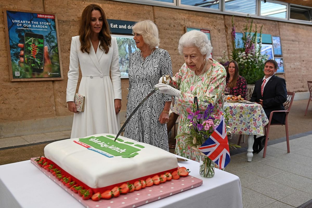 Britain's Queen Elizabeth II (C) attempts to cut a cake with a sword, lent to her by The Lord-Lieutenant of Cornwall, Edward Bolitho, to celebrate 'The Big Lunch' initiative at The Eden Project, near St Austell in south west England on June 11, 2021.