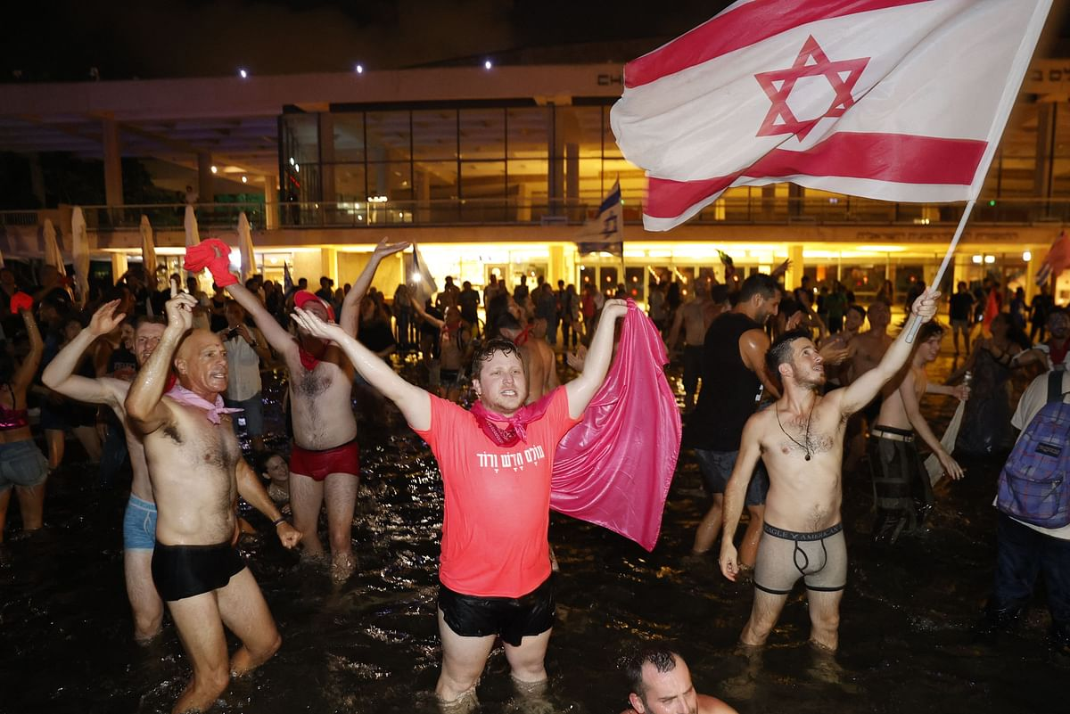 Israeli celebrate the passing of a Knesset vote confirming a new coalition government during a rally in Rabin Square in the Mediterranean coastal city of Tel Aviv on June 13, 2021.