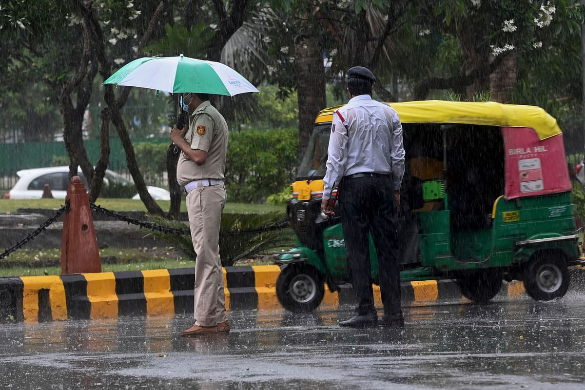 A traffic (R) policeman stands next to a colleague while overseeing traffic along a road during a monsoon rainfall in New Delhi on June 17, 2021.