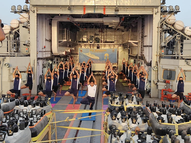 Indian Navy personnel perform Yoga on INS Shardul that is heading back from the Persian Gulf as part of the Operation Samudra Setu II deployment on the occasion of International Yoga Day 2021.