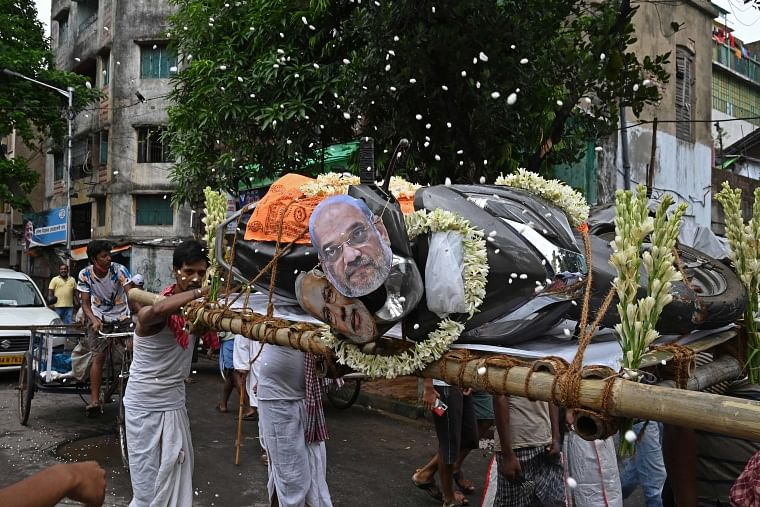 Activists mock a funeral procession of a petrol run vehicle with masks of Indian Prime Minister Narendra Modi and Indian Home Minister Amit Shah during a demonstration to protest against the rising fuel prices along a road in Kolkata