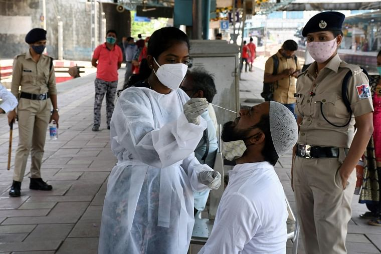A medic collects a swab sample of a passenger for the COVID19 test at Dadar railway station in Mumbai on Sunday