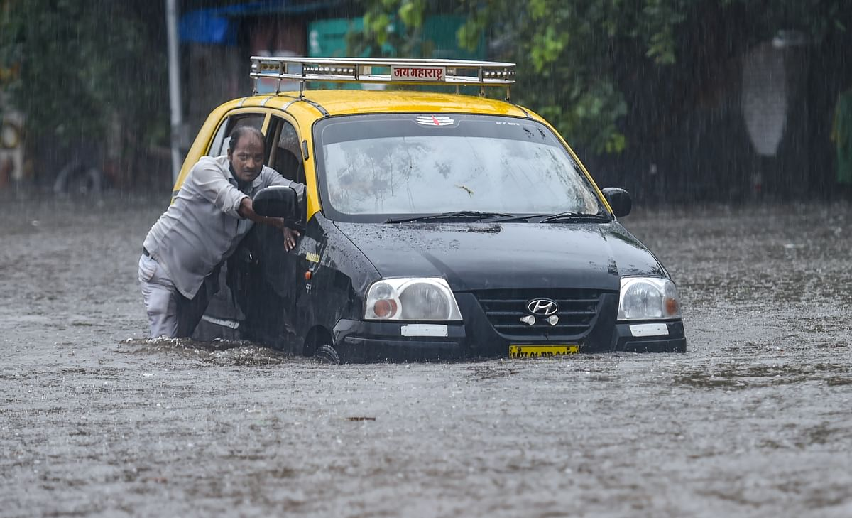 A taxi driver pushes his car as he tries to wade through a waterlogged street at Hindmata in Mumbai, Wednesday, June 9, 2021.