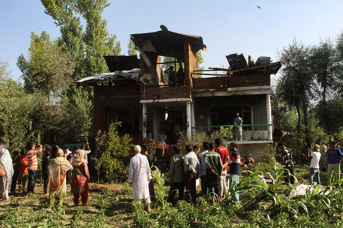 Kashmiri villagers gathered around a damaged house where a gun-battle occured between suspected militants and government forces in the Maloora locality on the outskirts of Srinagar in Jammu & Kashmir.
