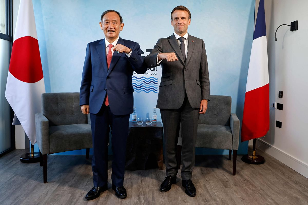 Frances President Emmanuel Macron (R) and Japans Prime Minister Yoshihide Suga (L) pose for a photograph before holding a bilateral meeting during the G7 summit in Carbis bay, Cornwall on June 12, 2021.