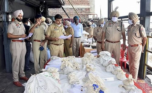Police officials display drug packets before disposing them on International Day against Drug Abuse, in Amritsar, Saturday.