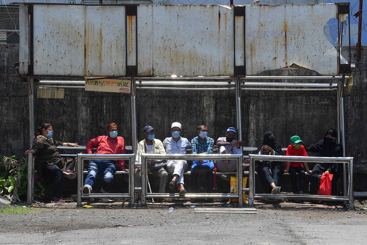 Commuters wearing facemasks as a protective measure against the spread of the Covid-19 coronavirus wait for their transport at bus stop in Mumbai on June 3, 2021.