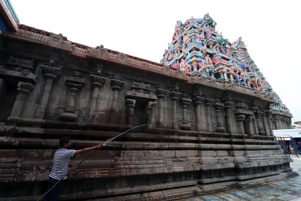 A worker washes the premises of Kapaleeshwarar Temple as the State government allowed the reopening of temples after COVID-19 relaxations.