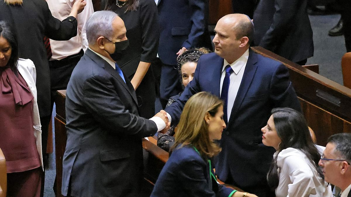 Israel's outgoing Prime Minister Benjamin Netanyahu shakes hands with his successor, incoming Prime Minister Naftali Bennett, after a special session to vote on a new government at the Knesset in Jerusalem, on June 13, 2021.