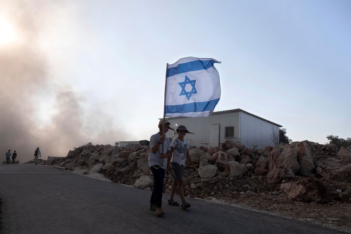 Eviatar: Israeli youths carry flags at the outpost of Eviatar near the northern West Bank town of Nablus, Monday, June 21, 2021.