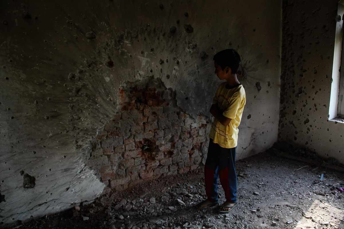 A Kashmiri boy stands next to the bullet-ridden wall inside the house that was damaged during a gunfight between security forces and militants in Maloora locality on the outskirts of Srinagar, Jammu & Kashmir.