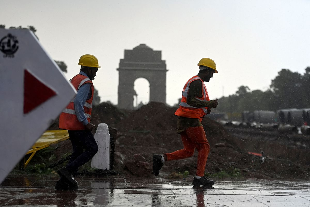 Construction workers run towards a shelter during a monsoon rainfall near India Gate in New Delhi on June 17, 2021.