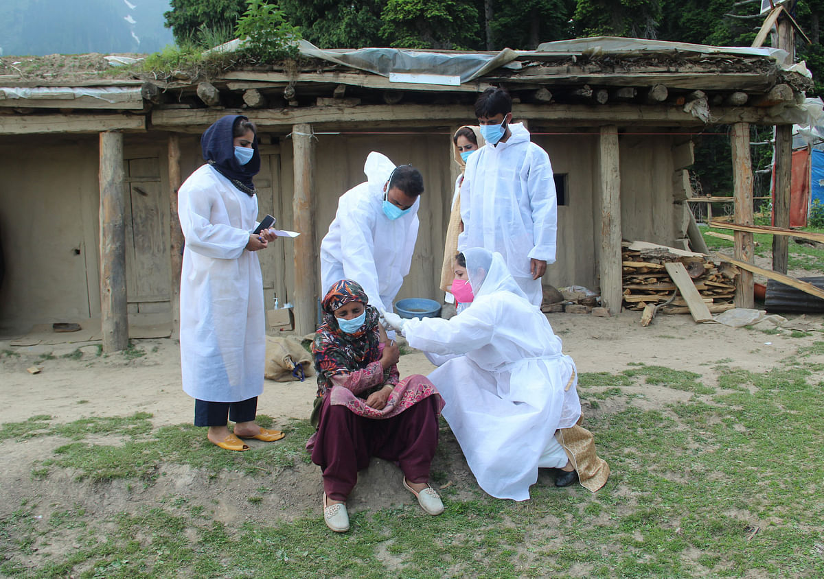 A healthcare worker gives a dose of Covishield, a coronavirus disease (COVID-19) vaccine to a nomadic woman during a vaccination drive in the forest area of Central Kashmir's Budgam district.