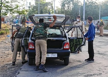 Cops check a vehicle amid  48-hour high alert in J&K ahead of PM Modi's all-party meeting.