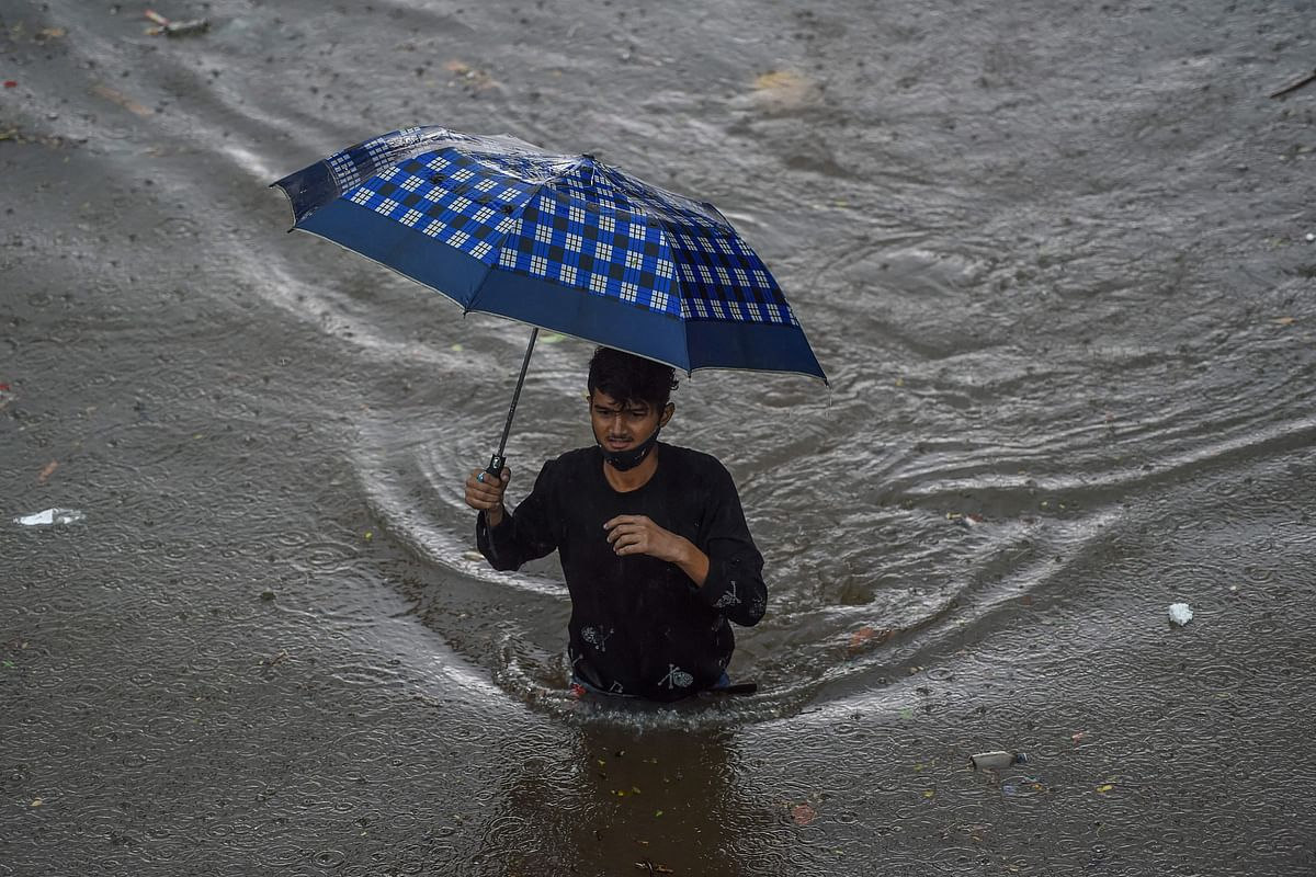A man walks on a flooded road during heavy monsoon rains in Mumbai on June 9, 2021.