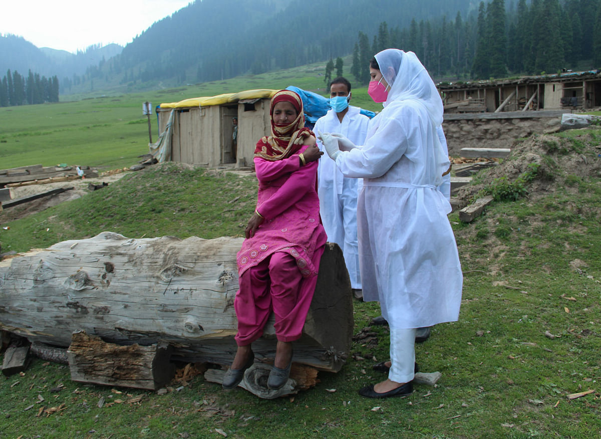 A healthcare worker gives a dose of Covishield, a coronavirus (COVID-19) vaccine to a nomadic woman during a vaccination drive in the forest area in Central Kashmir's Budgam district.
